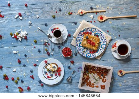 Sweet breakfast. Baked pea and pie dessert with red currant, raspberry and bluberries. Beautiful food served at blue rustic wooden table on white porcelain plates, tea and coffee cups. Top view