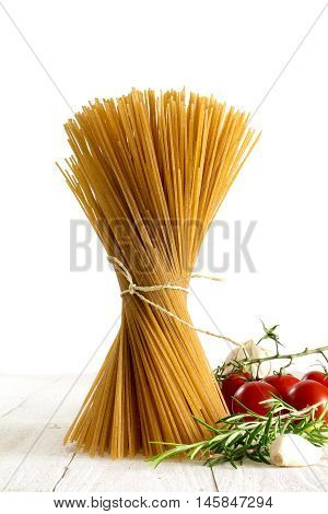 bunch of wholemeal spaghetti standing on white wood with some tomatoes and herbs isolated against a white background copy space selected focus