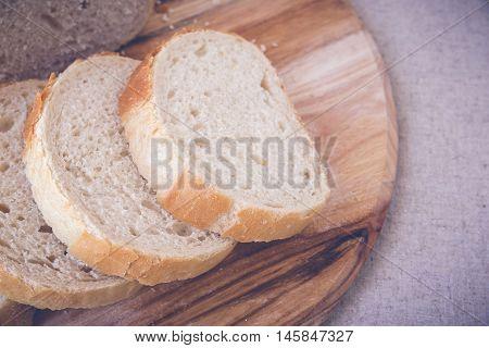 Sliced sourdough bread on wooden board, toning