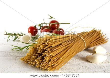 bunch of whole wheat spaghetti pasta on white wood with some tomatoes garlic and rosemary herbs against a white background with generous copy space selected focus narrow depth of field