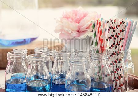 blue drink bottles with paper straws Alice in wonderland tea party themetoning