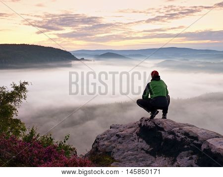 Tourist In Red Cap And Sportswear In Squatting Position On Rock
