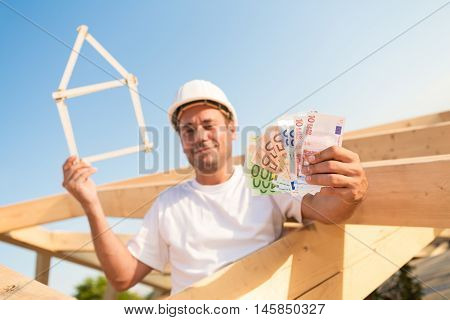 Young man with Euro banknotes and a symbolic house in his hands