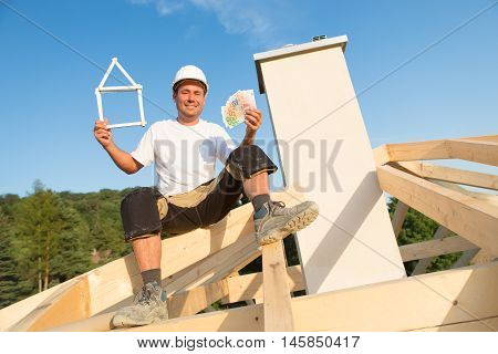 Young man is happy with new house and money in his hands