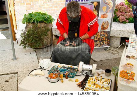 Kaliningrad Russia - August 3 2016: Craftsman makes and sells jewelry made of amber near Museum of Amber in Kaliningrad