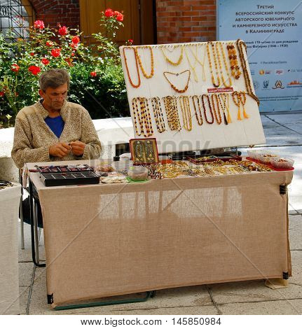 Kaliningrad Russia - August 3 2016: Craftsman sells jewelry made of amber near Museum of Amber in Kaliningrad