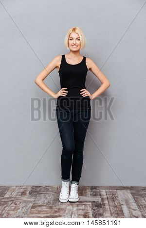 Full length of cheerful attractive young woman standing and smiling over gray background
