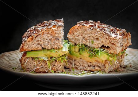 Sandwich with Guacamole, cheese and sprouts on whole grain rusk