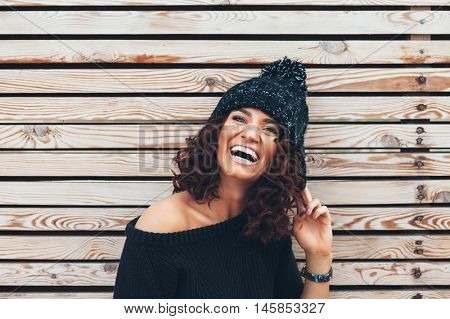 Hipster girl with curly hair wearing black sweater and hat posing against wooden wall, swag street style, autumn outfit