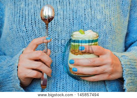Milky dessert with kiwi and nuts in the hands of a girl in a blue sweater