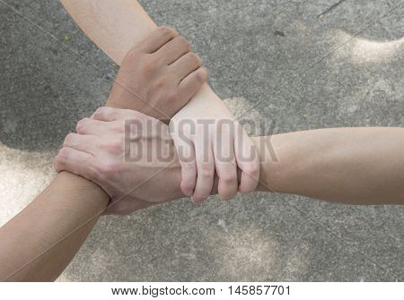 Man and women join hand together on the street under sunlight in the afternoon (Teamwork concept)