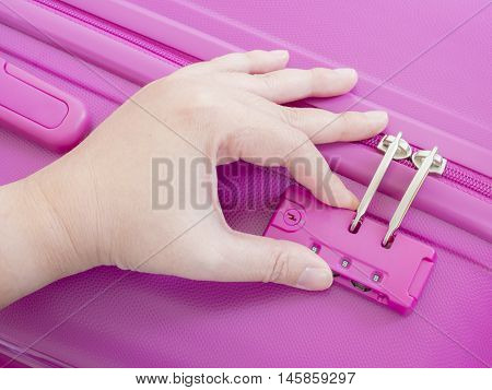 Woman use left hand to lock zipper on pink suitcase