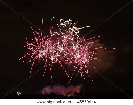 Huge red fireworks with ferries wheel to the left and crazy shaped bursts - celebrating New Year or other festivities - abstract holiday background with copy space for your text