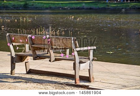 Rustic wooden park bench by the river draped in faded pink party decorations. Audley, Royal National Park, Australia