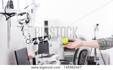 mechanized robot hand holds the objects drawn to a man's hand shaking hands