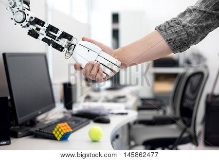 Science University, Kaliningrad, Russia, August 6, 2015mechanized robot hand holds the objects drawn to a man's hand shaking hands