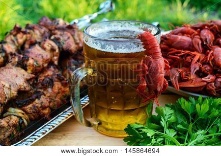 Foamy beer in a glass and boiled crawfish grilled meat on skewers in the background. For the holidays enjoying the outdoors.