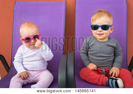 Cute boy and girl twins sitting on chairs in sun glasses