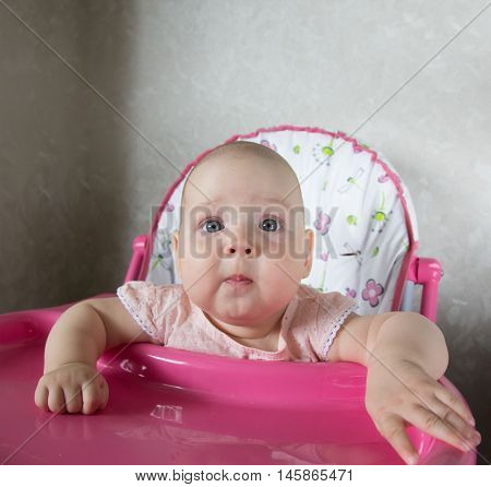 Portrait of a baby sitting in a highchair