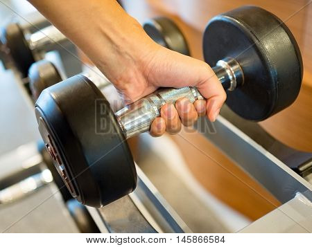 Woman hold dumbbell weights at gym ready for weightlifting exercise.