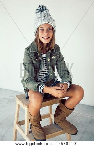Fashion pre teen girl of 10 years old wearing fall clothing and boots, hipster style