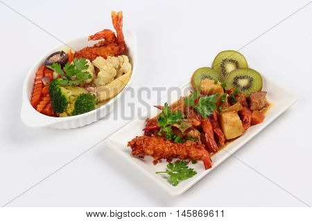 Deep fried shrimp in Japanese style topped yellow curry served with fried mixed vegetables on white background. Side view.