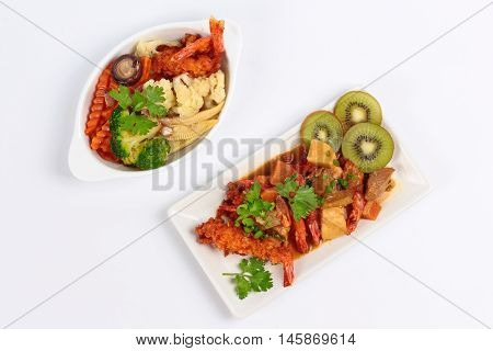 Deep fried shrimp in Japanese style topped yellow curry served with fried mixed vegetables on white background. Top view.