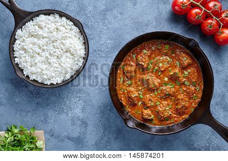 Madras butter Beef spicy slow cook lamb food with rice and tomatoes in cast iron pan on blue table background. Delicious India culture restaurant dish.