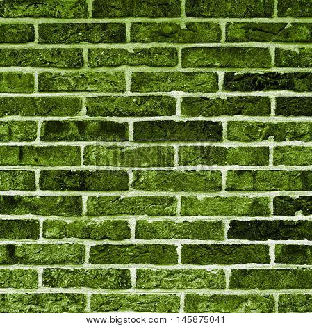 Background of Green and Black Bricks with Cracked Surface and Concrete closeup Outdoors