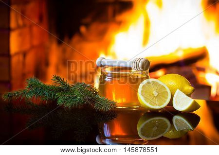 Christmas New Year composition. Jar of bee honey, lemon with christmas decoration - fir branches in front of warm fireplace. Relaxed, magical, cozy atmosphere near fireplace