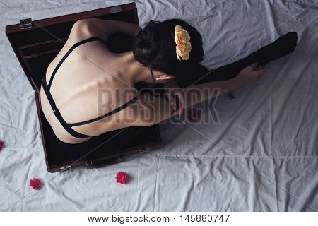 rear view of a ballerina sitting in a suitcase
