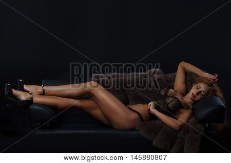 Woman in lingerie posing on a dark background in the studio