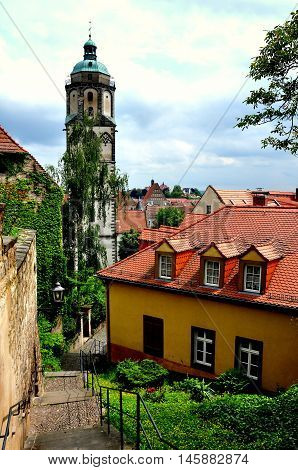 Meissen Germany - May 28 2013:: A stairway winds past old walls a baroque church tower and houses with orange roofs in the city's historic district