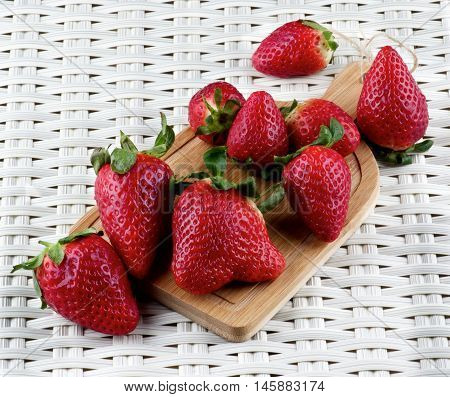 Heap of Fresh Ripe Strawberries on Small Wooden Cutting Board closeup on Wicker background