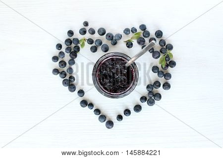 flat layout with blueberry heart of berries around an open the jar berry jam with a spoon top view / favorite treat jam from forest berries