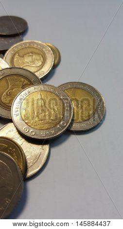 Thai baht coins on white paper. focus on ten baht coin.