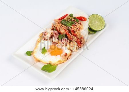 Rice topped with stirred  minced-pork ,squid ,basil and fried egg(sunny up) on white background.