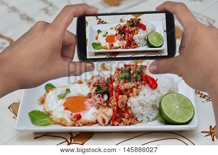 Using mobile phone to take photo a dish of  rice topped with stirred meat and basil for share to social network. Selective focus.