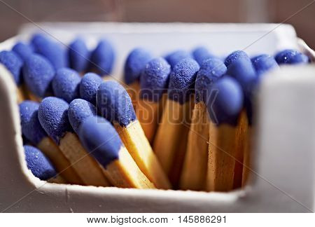 Macro detail of safety match sticks with blue heads in the paper match box (matchbox) in the shape of typical cigarette box