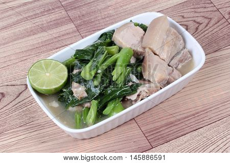 Fried Chinese kale and streamed streaky pork in soup on wood.