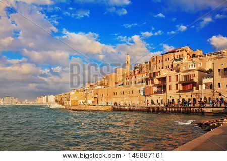 TEL AVIV, ISRAEL - NOVEMBER 22, 2014: Sunny day. On the promenade people stroll and relax. The ancient port of Old Jaffa, Tel - Aviv