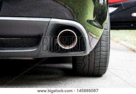 Sport Car muffler in the back of a black luxury sport car.