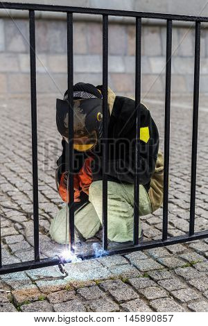 Welder welds on the fence railings. Wear protective clothing and a black mask