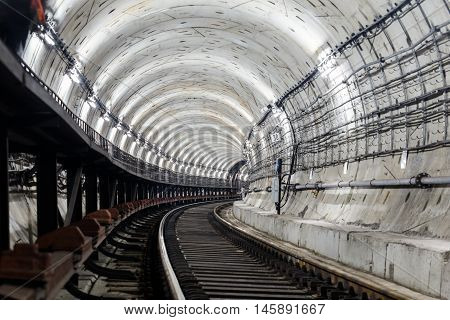 circular tunnel subway with rails and sleepers turns right and is illuminated with white light.