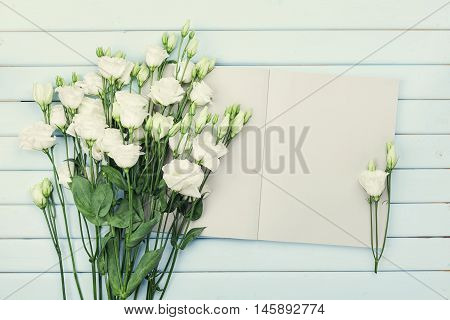 Open empty notebook and bouquet of white flowers eustoma on blue rustic table from above. Woman working desk. Flat lay styling.