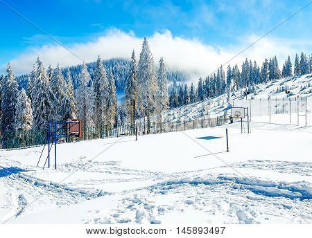 Basketball court in beautiful mountain snowy landscape