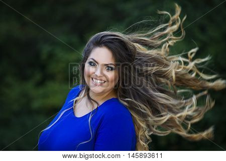 Young beautiful caucasian plus size model in blue dress outdoors xxl woman on nature with developing in the wind hair professional makeup and hairstyle