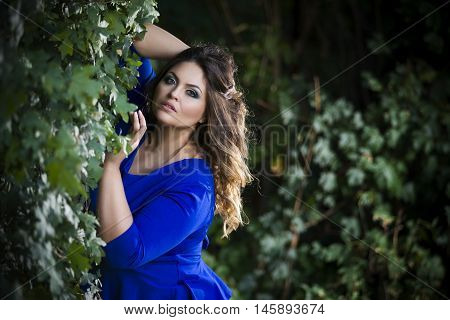 Young beautiful caucasian plus size model in blue dress outdoors xxl woman on nature professional makeup and hairstyle