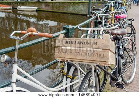 NETHERLANDS - AMSTERDAM - CIRCA MARCH 2014: Bicycle standing against a bridge railing in Amsterdam.