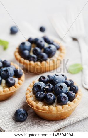 Tartlets with blueberries bilberry ricotta and honey syrup on gray vintage background. Delicious dessert.